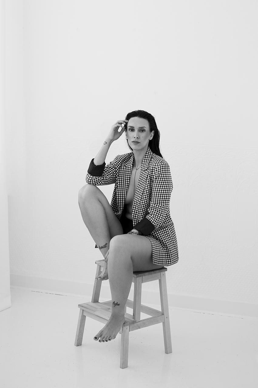 Frau sitzt in Dessous auf einem Stuhl für ein Selbstliebe Fotoshooting