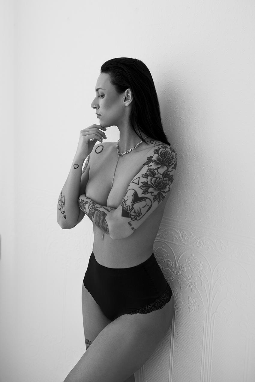 Frau steht in Unterwäsche an einer Wand für Boudoir fotos
