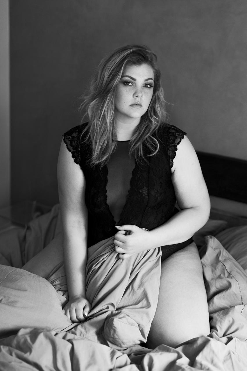 Frau sitzt in Unterwäsche auf einem Bett für ein Boudoir fotoshooting
