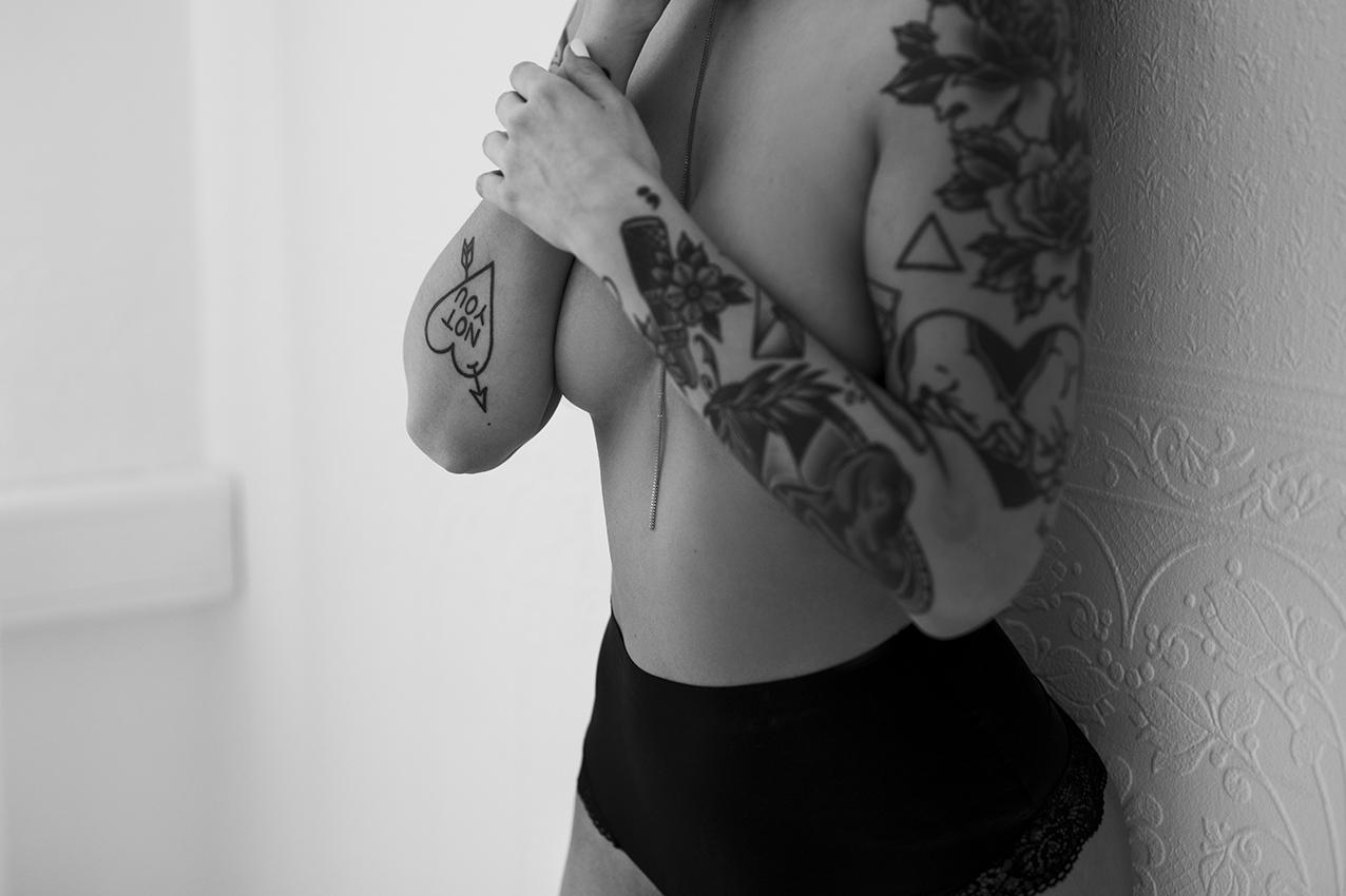 Tattowierte Frau steht mit Rücken an der Wand für ein Boudoir fotoshooting