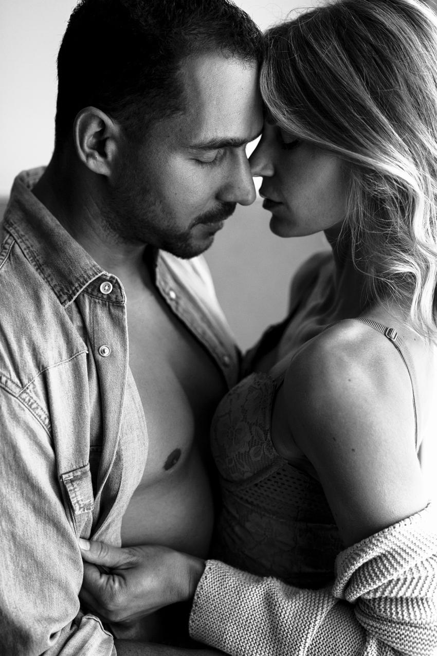 Paar steht in Unterwäsche am Fenster für ein coupleboudoir fotoshooting