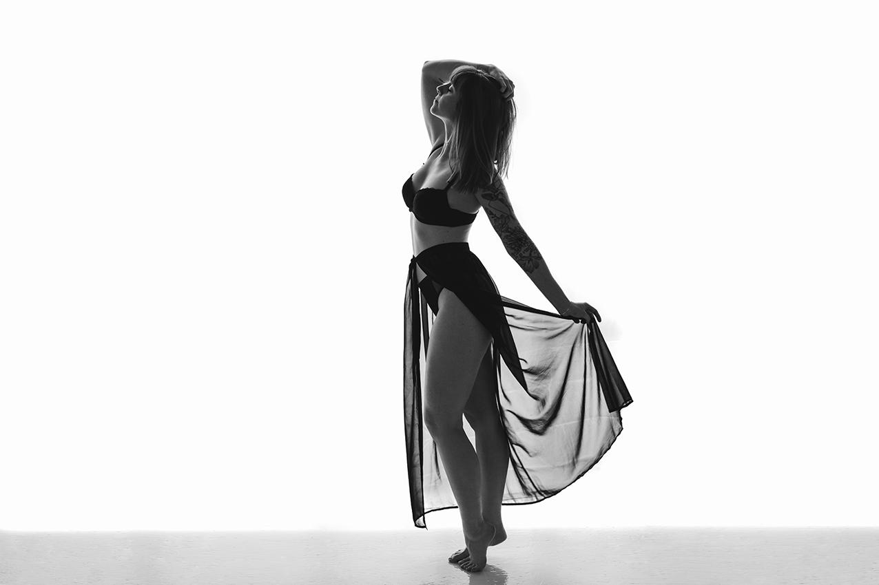 Frau steht in Unterwäsche am Fenster für ein Boudoir fotoshooting