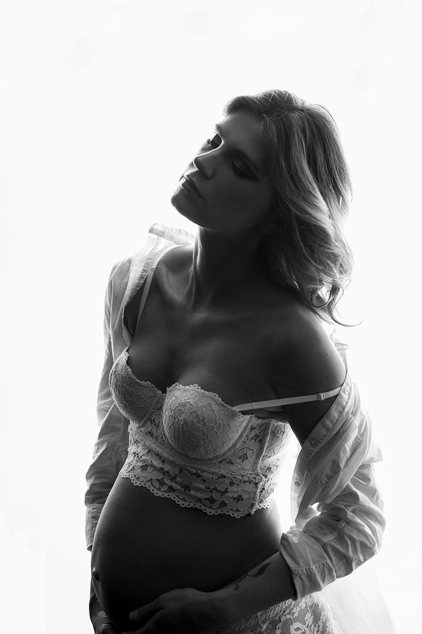 Frau steht in Unterwäsche am Fenster für ein Boudoirfotoshooting