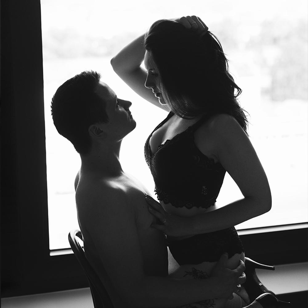 Paar sitzt in aufreizender Pose auf einem Stuhl vor einem Fenster für ein Couple Boudoir Fotoshooting