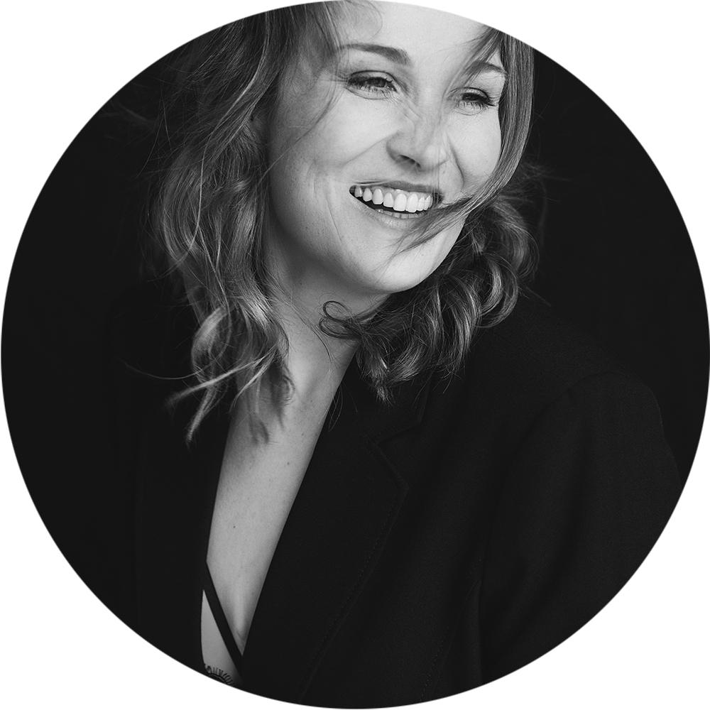 Frau sitzt lachend vor schwarzem Hintergrund