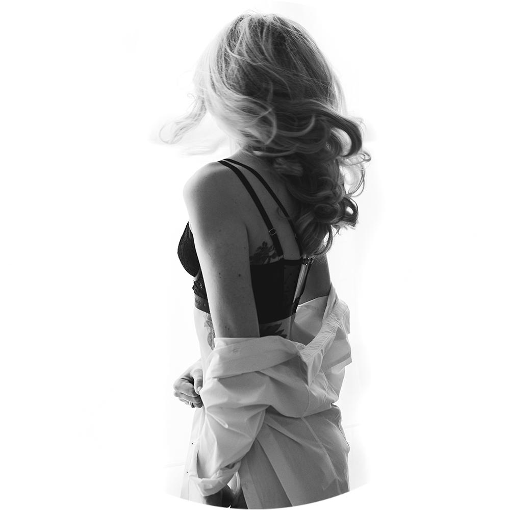 Frau steht in Unterwäsche vor hellem Hintergrund für ein Boudoir fotoshooting