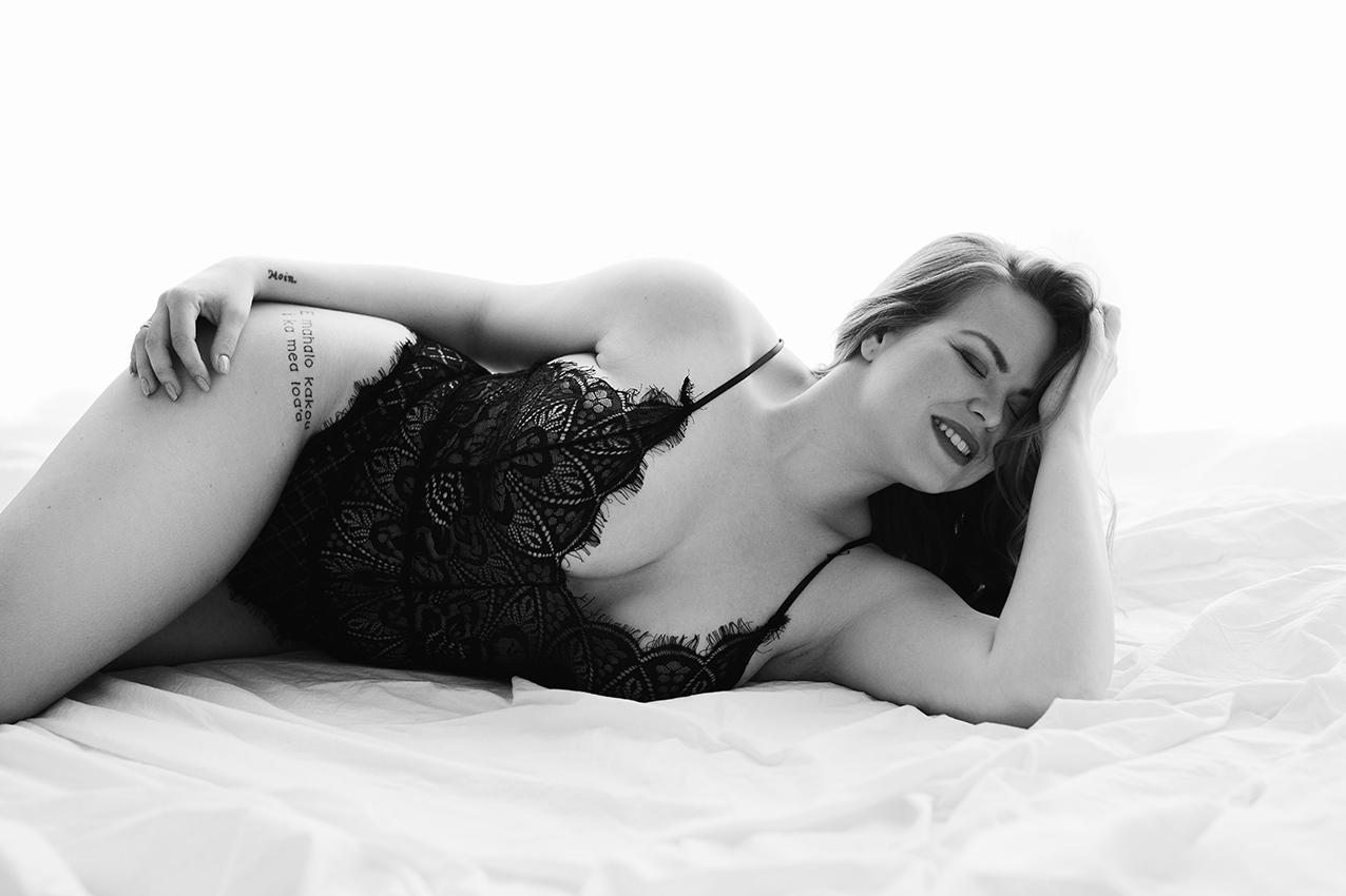 Frau liegt in Unterwäsche auf einem Bett für ein Boudoir fotoshooting