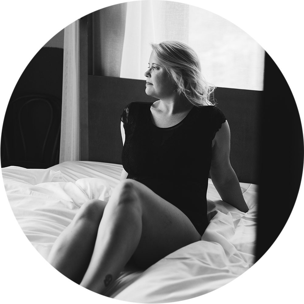 Frau sitzt in Unterwäsche auf einem Bett für ein Boudoirfotoshooting