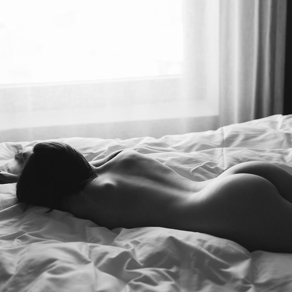 Frau liegt nackt auf einem Bett für ein Boudoirfotoshooting