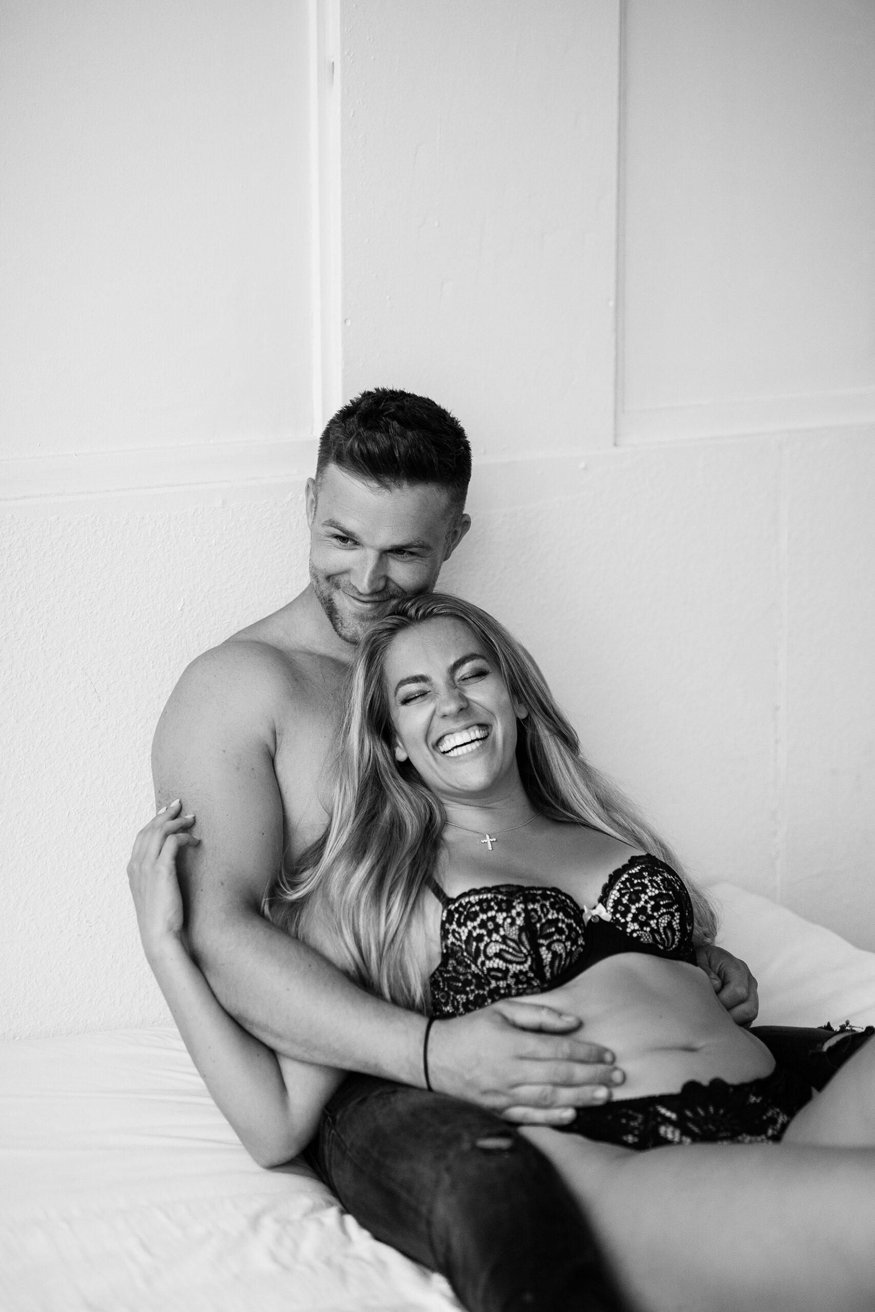 Paar liegt in Dessous auf einem Bett für Couple Boudoir fotos