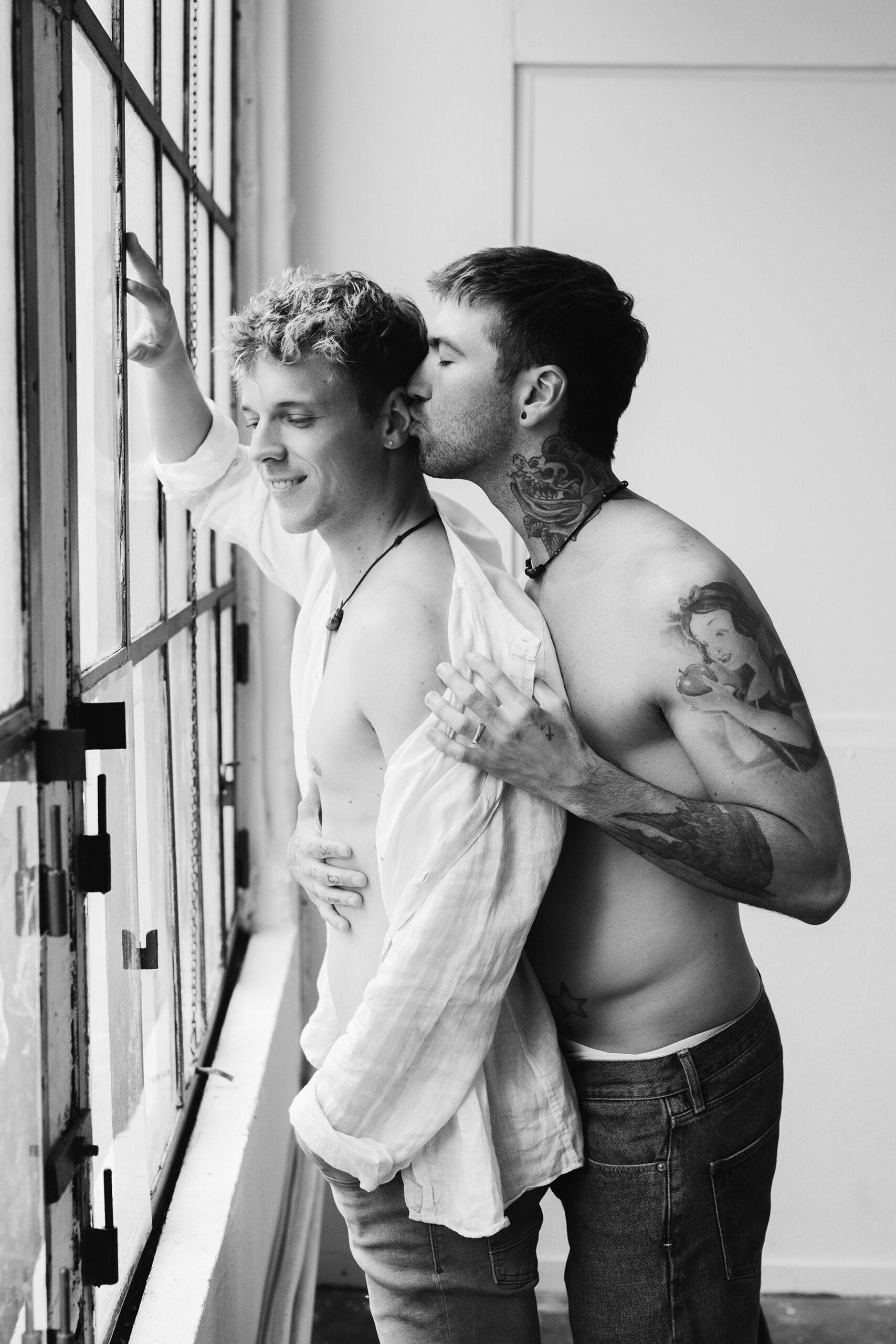 Schwules Paar steht vor Fensterwand für Couple Boudoir fotos